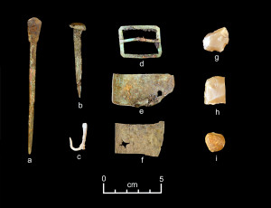 A representative collection of artifacts discovered in J uly 2015. (a) one leg of a brass nautical divider for measuring distances on charts; (b) a copper ship 's nail; (c) a fishhook possibly made from a copper nail; (d) a brass or copper belt or strap buckle; (e) perforated sheet copper, possibly from hull sheathing; (f) perforated sheet copper, possibly from hull sheathing; (g) French gunflint; (h) French gunflint; (i) lead musket ball. Ph otos by Dave McMahan.